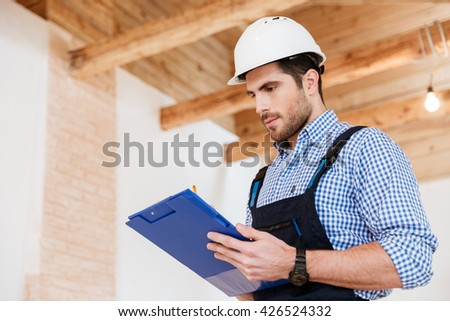 Happy builder writing something in hardhat with clipboard in his hands - stock photo