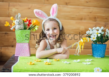 Happy bunny girl with easter eggs sitting in country house and celebrating holiday - stock photo