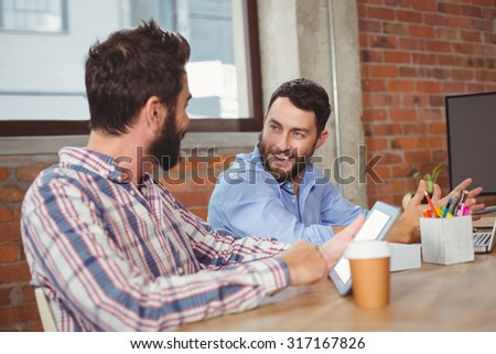 Happy business colleagues talking in creative office - stock photo