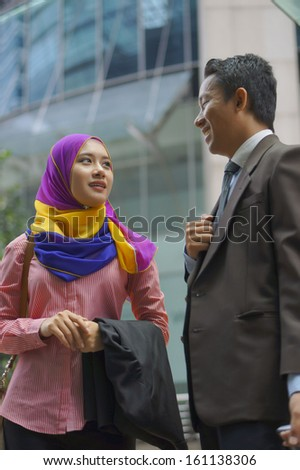 Happy Business colleagues walking outside office - stock photo