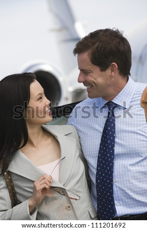Happy business couple looking each other at airfield - stock photo