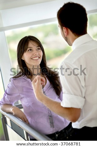 Happy business couple talking  and smiling indoors - stock photo