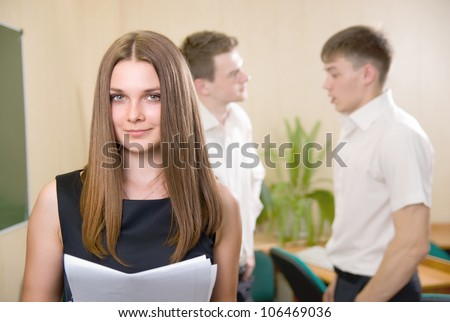 Happy business girl with colleagues at the back. - stock photo