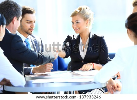 Happy business man and woman shaking hands - stock photo