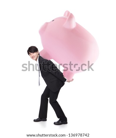 happy business man carrying pink piggy bank on his back in full length isolated on white background, asian model - stock photo
