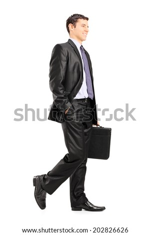 Happy business man holding a briefcase and walking isolated on white background - stock photo