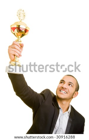 Happy business man holding a trophy aloft - stock photo