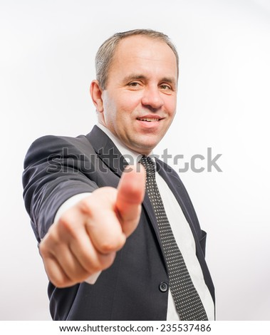 Happy business man holding thumbs up - stock photo