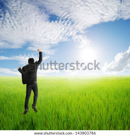 Happy business man jumping in green rice field and clouds sky - stock photo