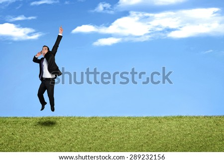 Happy business man jumping in landscape - stock photo