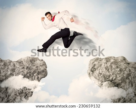 Happy business man jumping over a cliff concept - stock photo