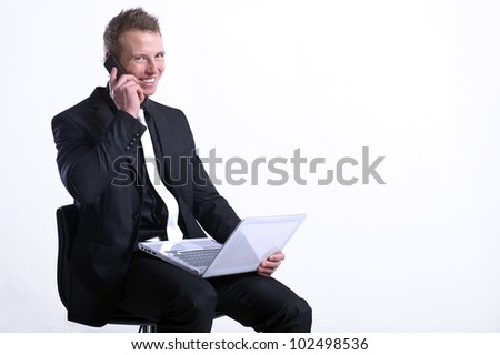 Happy business man on cell phone in front of laptop - stock photo