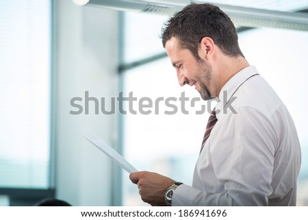 Happy business man reading papers in office - stock photo