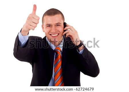 Happy business man showing thumb up while talking on the phone - stock photo