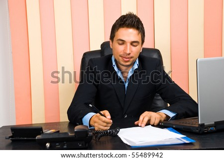 Happy business man sitting at desk in office and write on paperwork