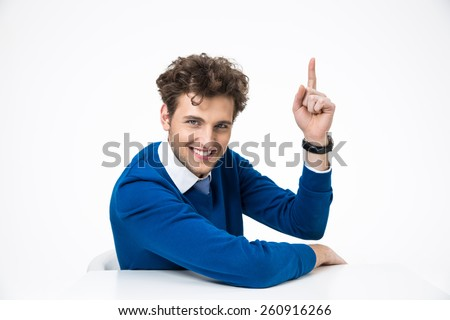 Happy business man sitting at the table and showing finger up - stock photo