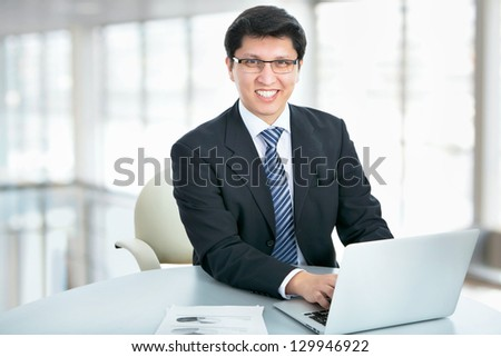 Happy business man sitting in front of laptop - stock photo