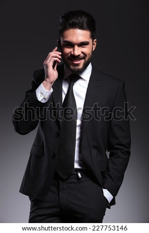 Happy business man talking on the phone, holding one hand in pocket while smilng for the camera.
