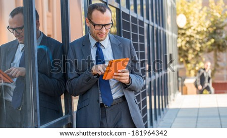 Happy business man using tablet PC in orange cover on a city street - stock photo