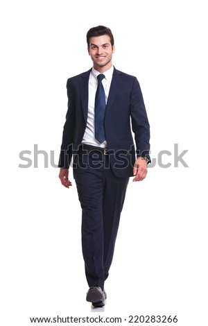 Happy business man walking on white studio background, smiling to the camera - stock photo