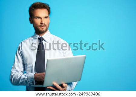 Happy business man with a laptop - isolated over a blue background - stock photo