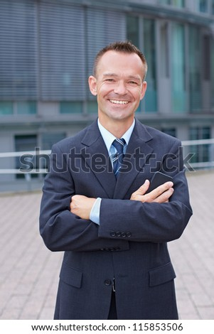 Happy business man with arms crossed outside of his office - stock photo
