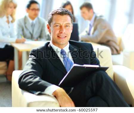 Happy business man with colleagues at a conference in the background - stock photo
