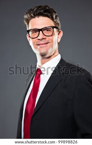 Happy business man with grey suit and red tie isolated on dark background. Wearing retro glasses. Studio shot.
