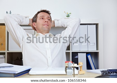 Happy business manager in office relaxing and leaning back - stock photo