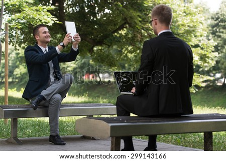 Happy Business Men Using Tablet Pc Outside On A Park Bench