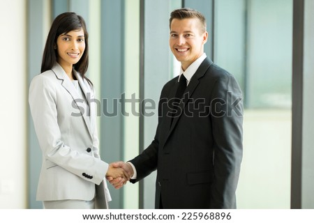happy business partners handshaking in conference hall - stock photo