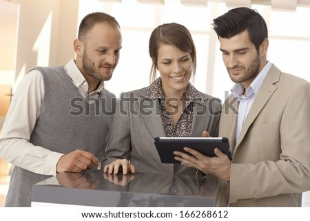 Happy business partners standing at table looking at tablet in office. - stock photo