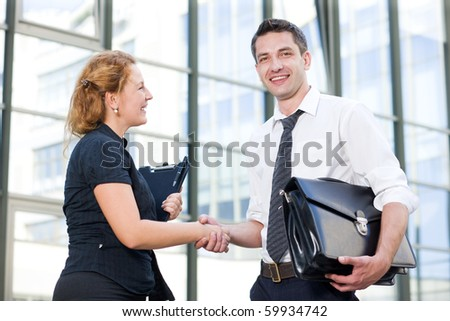 Happy business people greeting each other stock photo royalty free happy business people greeting each other outdoors red haired woman looking at her partner m4hsunfo