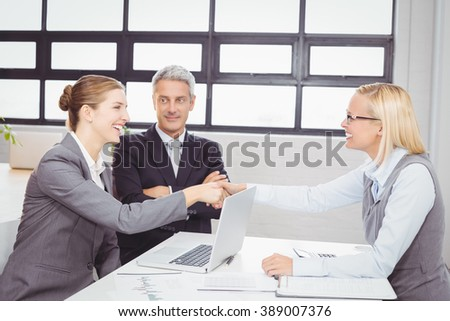 Happy business people handshaking with client in meeting room - stock photo