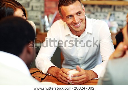 Happy business people having meeting around table in office - stock photo