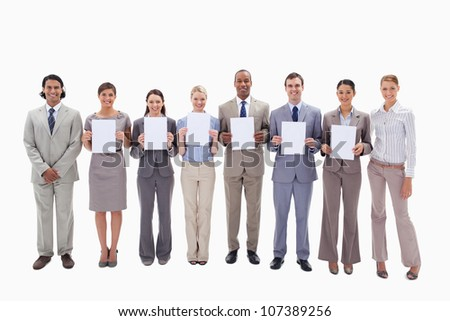 Happy business people holding six white supports for letters against white background - stock photo