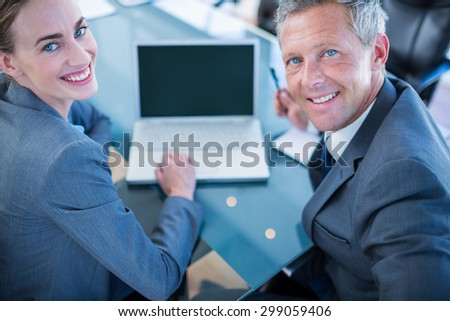 Happy business people looking at camera in office - stock photo