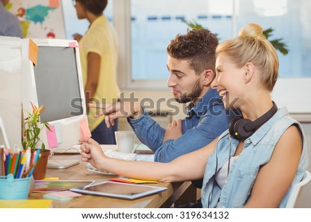 Happy business people looking at computer in creative office - stock photo
