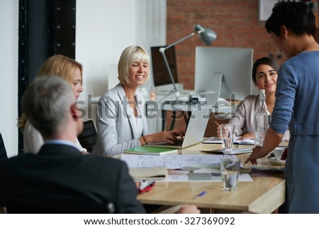 Happy Business people meeting around a boardroom table discussing creative concept