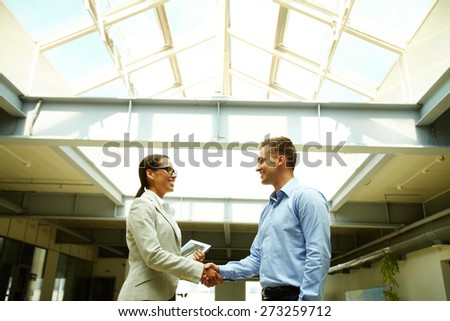 Happy business people shaking hands after striking deal - stock photo