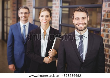 Happy business people standing in office - stock photo
