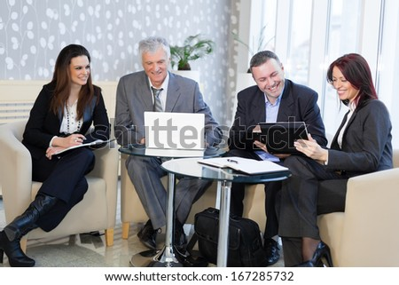Happy business people using laptop and talking about a work  - stock photo