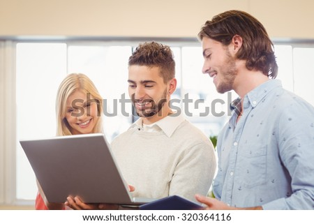 Happy business people using laptop in creative office - stock photo