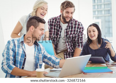 Happy business people working on laptop at desk in office