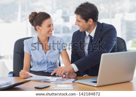Happy business people working together and smiling in the office - stock photo
