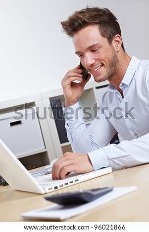 Happy business student working with laptop computer and cell phone - stock photo