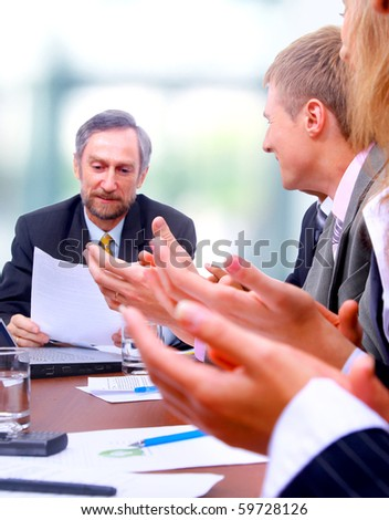Happy business team applauding together - stock photo