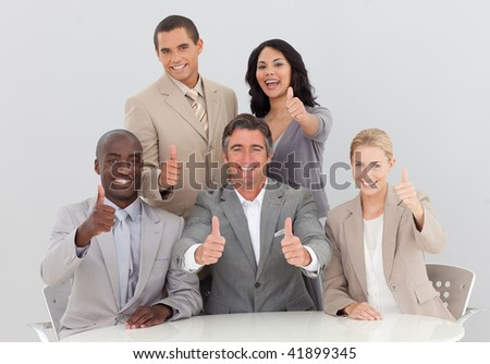 Happy business team celebrating a success with thumbs up in the office - stock photo