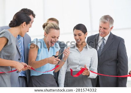 Happy business team cutting red ribbon in the office - stock photo