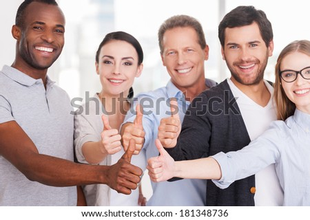 Happy business team. Group of cheerful business people in casual wear standing close to each other and showing their thumbs up - stock photo